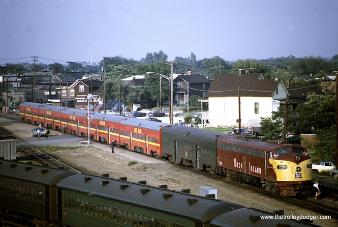 "On August 13, 1971 Chicago Rock Island & Pacific #303 and 125 are backing into Blue Island (Burr Oak) yard. Bill Shapotkin adds, ""The train is a ROCK Mainline Suburban train (if it had operated via Beverly, it would be west of the depot (to left)."""