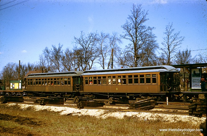 "In this original red border Kodachrome slide, we see a two-car train of CTA wooden ""L"" cars, possibly on a fantrip, on the ground-level section of the Garfield Park ""L"" (possibly Central or Austin?). The date is April 14, 1957. In the foreground, we see a new temporary track alignment under construction."