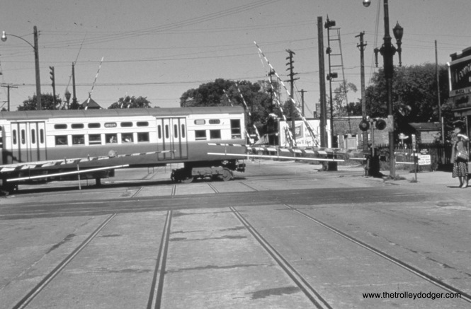 Garfield Park trains crossing DesPalines Avenue at grade in Forest Park. Tracks in the foreground were once used by West Towns Railways streetcars.