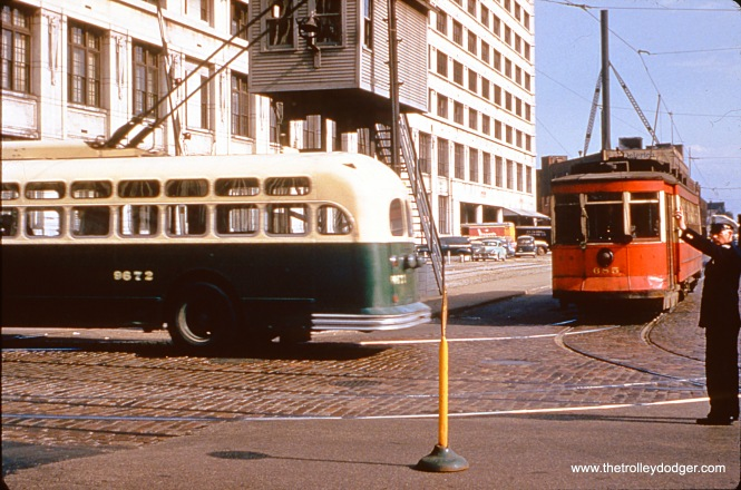 CTA trolleybus 9672 and red Pullman 685 are near the Montgomery Wards complex at Chicago and Larrabee. This would be a Halsted streetcar, running on diversion trackage via Division to Crosby and Larrabee, then Chicago to Halsted, when work was being done on the Halsted Street bridge over the Chicago River. That dates the picture to 1953-- after Marmon trolleybuses were delivered, but before streetcars stopped running on Halsted in 1954. (William Hoffman Photo, Wien-Criss Archive)