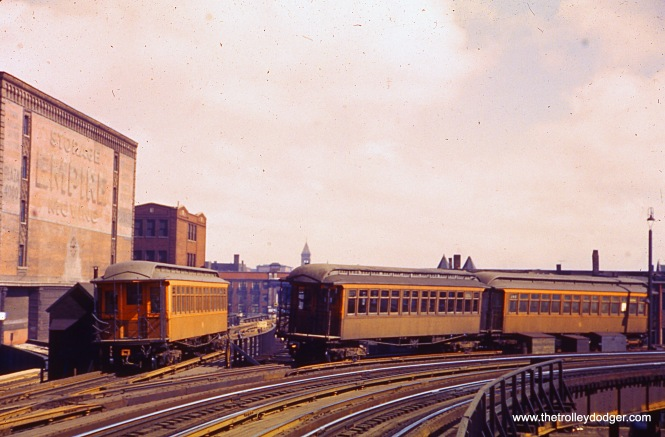 "We are looking east off the CTA's Indiana Avenue ""L"" station in the early 1950s. At left, a Kenwood train has just departed en route to 42nd Place. At right, two 200-series cars (used as equipment on the Kenwood line) are in storage on what once had been the northbound local track of the South Side ""L""."