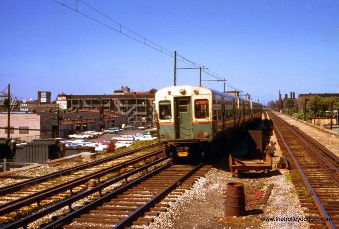 "A southbound Howard ""A"" train is on the center track. and served stations that either had a center platform or (like Wilson) had two sets of platforms. ""B"" trains (and the Evanston Express) used the outer tracks and served stations with side platforms. This picture was taken in May 1968. Note the southbound outer track has overhead wire in addition to third rail, for use by freight trains that ran at night until 1973. George Trapp: ""Southbound Howard to Englewood ""A"" train has two cars of 6511-6550 series on head end. This series was split between the North-South and West-Northwest in the 1960's with cars up to 6550 and 6551-6558 from next series being on North-South in winter months. Note that track 4 was being redone at that time and is missing."""