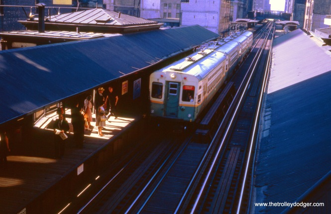 "In September 1964, a four-car Evanston Express train approaches (I think) the old station at State and Van Buren. All four cars are single car units equipped with trolley poles, for use in Evanston where local laws did not permit use of third rail for current collection. In the early 1970s, this station was closed and removed, but was eventually put back, to serve the Harold Washington Library. This leg of the Loop ""L"" had a continuous platform for some time, which is visible here. George Trapp: ""The September 1964 photo of four single unit cars 25-28, 39-50 on the Evanston Express are at Madison & Wells not State & Van Buren. Note crossover at Washington where non rush Ravenswood and late AM Evanston Expresses crossed over to the Inner Loop after stopping at Randolph & Wells on the Outer Loop. There was also a long continuous platform from Randolph to Madison."""