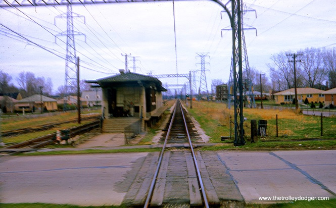 "From 1925 until 1948, the Niles Center line provided local ""L"" service between Howard and Dempster on tracks owned by the North Shore Line. There were several stations along the way, and here we see one of them, as it appeared in September 1964 before it was removed to improve visibility at this grade crossing. I would have to check to see just which station this was, and whether the third track at left was simply a siding, or went to Skokie Shops. Miles Beitler says this is the ""Kostner station looking east. The third track on the left was simply a siding, a remnant of North Shore Line freight service."""