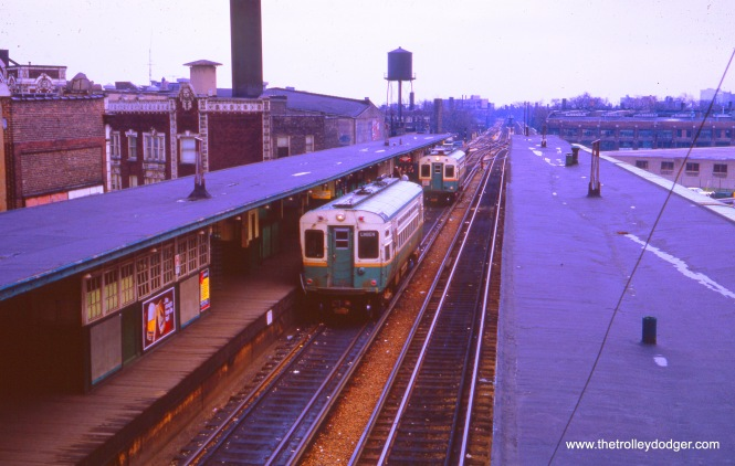 Two single car units in October 1966, both equipped for overhead wire, but for different purposes. In the foreground, an Evanston shuttle car has trolley poles, while the Skokie Swift car at rear uses pantographs. Evanston was converted to third rail in 1973, and the Swift about 30 years after that.