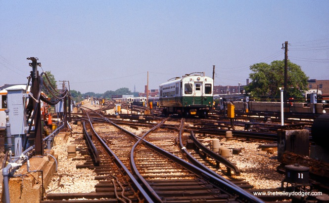 A CTA single-car unit, equipped with trolley poles, is running on the Evanston branch near Howard on May 28, 1977. Although overhead wire was no longer being used on Evanston, poles were left on a few such cars to serve as backups on the Skokie Swift if needed.