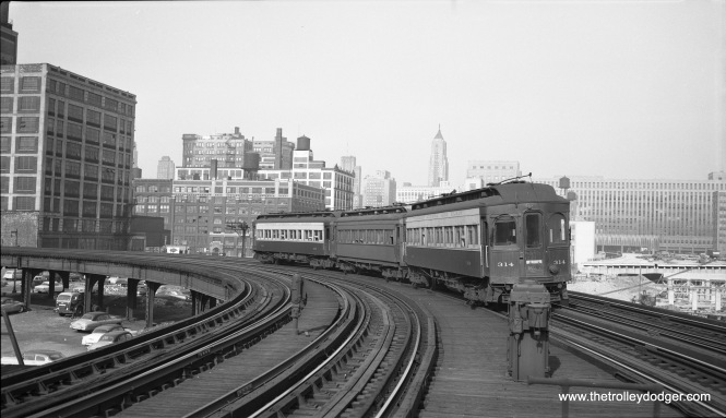 "A three-car Chicago Aurora & Elgin train , including cars 316 and 314, as seen from the Halsted Street platform of the Garfield Park ""L"". The view looks east on June 18, 1953, about three months before CA%E service was cut back to Forest Park. (Robert Selle Photo)"