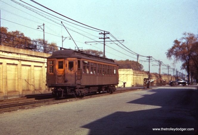 "A single CTA wooden ""L"" car heads east on the ground-level portion of the Lake Street ""L"" circa 1955. This was relocated onto the adjacent Chicago & North Western embankment in 1962."
