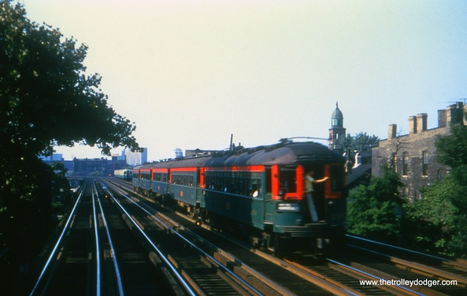 A five-car CNS&M train on Chicago's north side. In the days before air conditioning became standard on rapid transit cars, a rider holds the door open on a hot day to take advantage of the breeze.