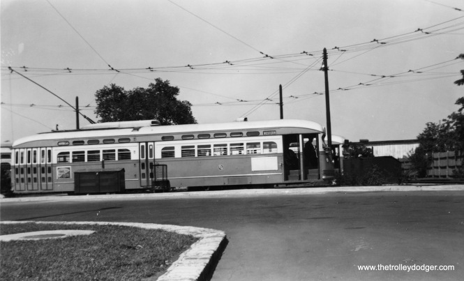 "When we see pictures of Western Avenue PCC cars, the question is usually, which terminal is this? Berwyn and 79th had very similar turnaround loops, built around the same time (and still used today by buses). Since the buildings at rear do not match those seen at Berwyn, I am going to say this is Western and 79th. M.E.: ""This has to be 79th, for two reasons: (1) Photos I have seen of the Berwyn terminal have more vegetation. (2) In the foreground of this picture are bus lanes. I don't remember any bus service at Berwyn. On the contrary, both the 49A South Western and both lines on 79th St. (route 79 east to the lake, and route 79A west to Cicero) used this terminal."""