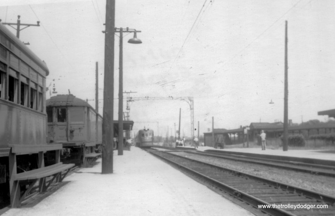 "A North Shore Line Electroliner is off in the distance, making a stop at... where? Scott Greig: ""The southbound Electroliner with the MD car at far left is looking northeast at Downey's-Great Lakes. MD cars were commonly used to move sailors' baggage, even after LCL service ended in 1947."" Joe Stupar: ""The Electroliner looks like it's at Great Lakes? Looks like a coach and an MD car in the pocket there."""