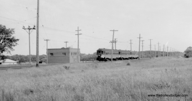 "A North Shore Line train ""at speed,"" as they used to say. Not sure where this is. Joe Stupar: ""The North Shore train at speed looks like it might be at 4 Mile Substation? The building looks similar, and this other photo of the south side shows a similar setup with the high tension wires coming over the building, and a simple tap with no steel structure."""
