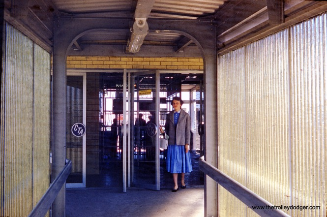 "On June 21, 1958 a woman enters the new CTA rapid transit station at Pulaski Road on the Congress line, which replaced the Garfield Park ""L"" the following day. On this day, free rides were given out between Halsted and Cicero Avenues. The fiberglass panels on the sides of the entrance ramp were eventually cut down to allow for better visibility from outside."