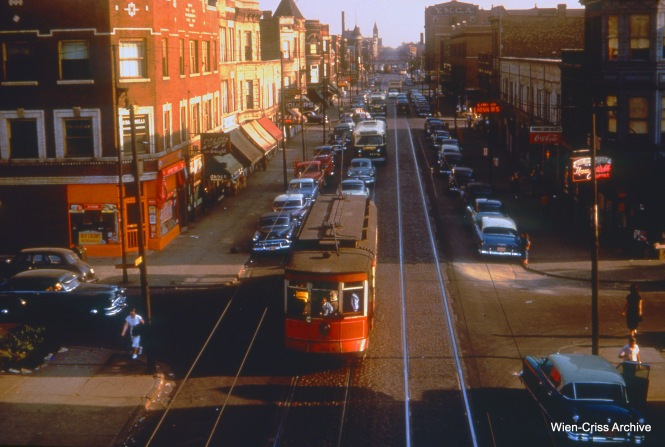 "CTA 128 is on Kedzie at the Garfield Park ""L"" on August 2, 1953. A couple of trolley buses are also visible."
