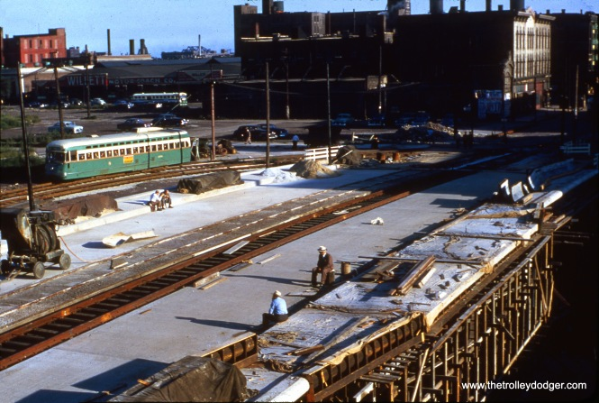 "We have run various other pictures showing the construction of the bridge at Halsted over what is now the Eisenhower (formerly Congress) Expressway, but not this one. It shows a Pullman-uilt CTA PCC, operating on Route 8, using the shoo-fly around the bridge construction site. The bridge was finished by 1953, so my guess would be this picture is circa 1952. The view looks to the southeast from the nearby Garfield Park ""L"" station, which was not directly in the expressway footprint, and remained open until 1958."