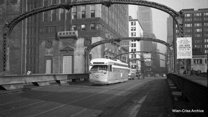 "CTA 4096 is westbound on Madison, crossing over the Chicago River. The Civic Opera House is to the left. The sign indicates that this bridge is going to be converted to ""one man operation,"" meaning that it will be operated from only one tower instead of two. (Wien-Criss Archive)"