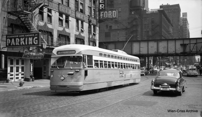 CTA PCC 4201, operating on Route 36 - Broadway-State, has apparently been diverted from State Street, possibly due to a parade, and is northbound on Dearborn at Lake Street. The car at right has a 1953 Illinois license plate, but when this picture was taken, Dearborn was still a two-way street, meaning it is prior to November 16. (Wien-Criss Archive)