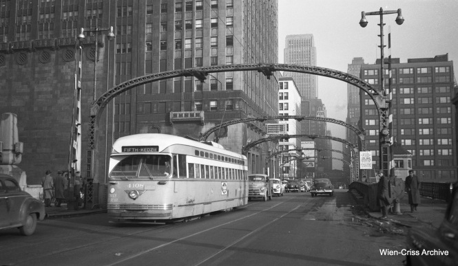 CTA PCC 4108 is westbound on Madison at the Chicago River, running on the Madison-Fifth branch of Route 20. The cars have 1953 license plates. PCCs were taken off Madison on December 13, 1953. For a few months, Madison-Fifth continued as a shuttle operation between Madison and Pulaski, using older red streetcars. The rest of Madison was bussed. (Wien-Criss Archive)