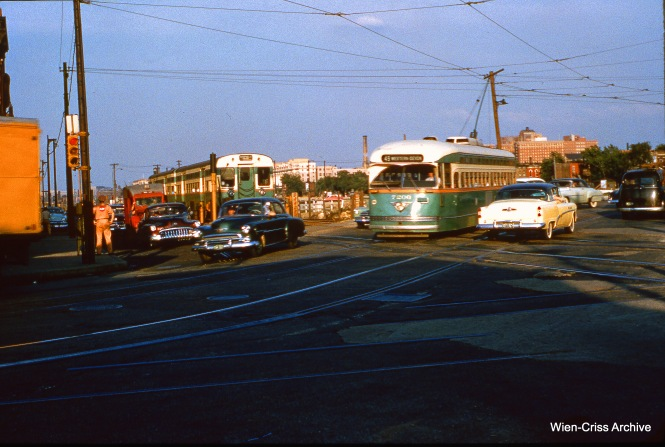 Northbound CTA PCC 7206 is on Western Avenue, passing a two-car train of PCC rapid transit cars on the Garfield Park temporary trackage in Van Buren Street. The date is June 16, 1954. (Wien-Criss Archive)
