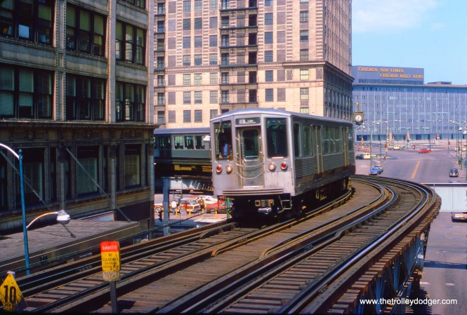 "This April 1975 view of Chicago's Loop ""L"" is notable, for three things in particular that are no longer there. The 2200-series railcars have been retired, the Sun-Times/Daily News building has been replaced by Trump Tower, and even the station where this photo was taken (Randolph and Wabash) is now gone."