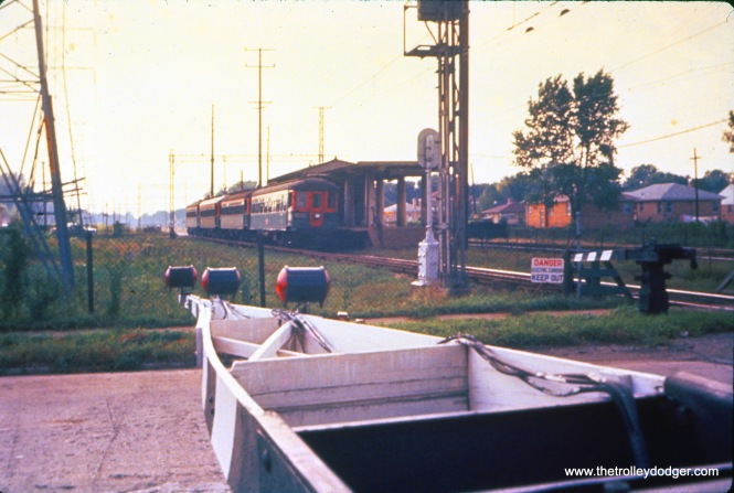 The crossing gates are down on August 18, 1959, as eastbound NSL train 220, made up of cars 725 and 719, prepares to cross East Prairie Road in Skokie (while passing a former rapid transit station). (John D. Horachek Photo, William Shapotkin Collection)