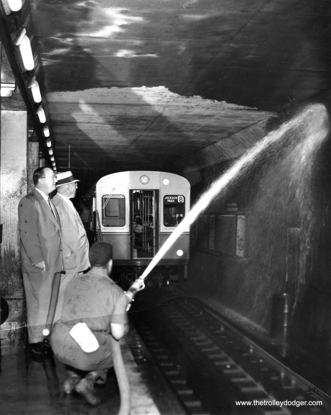 On July 26, 1955, a high pressure jet of water is used during cleaning of the CTA State Street Subway tube walls at the Roosevelt Road station. Virgil Gunlock (left) and H. L. Howell are inspecting the work.
