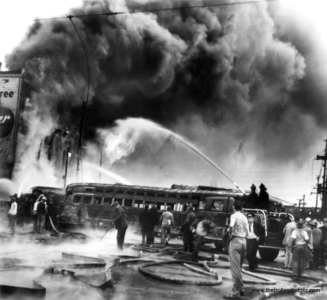 May 25, 1950: Firemen shoot (a) stream of water over burned-out streetcar into blazing building set afire by flaming gasoline, after the streetcar and tank truck (between streetcar and building) collided here.