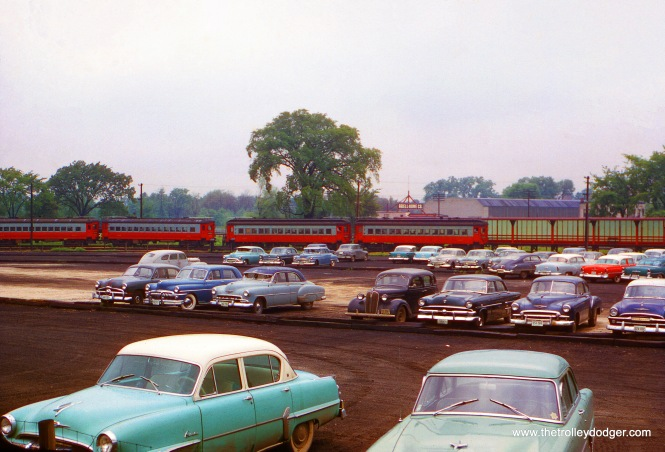 "On May 26, 1956, a two-car CA&E interurban train is at the DesPlaines Avenue Terminal in Forest Park. Another train is parked nearby on a small storage track. Between September 20, 1953 and July 3, 1957, CA&E trains terminated here, and riders who wanted to go downtown had to transfer across platform to CTA Garfield Park ""L"" trains. The track connection between the two lines had been severed, and each one turned around using a loop. The CTA's went above the CA&E on a wooden trestle. This view looks generally to the north. As of this time, construction of the nearby Congress (now Eisenhower) Expressway was planned, but heavy construction work had not yet started here. As it was, when this picture was taken, the CA&E had still not sold their right-of-way crossing the DesPlaines River, a short distance west (left) of here."