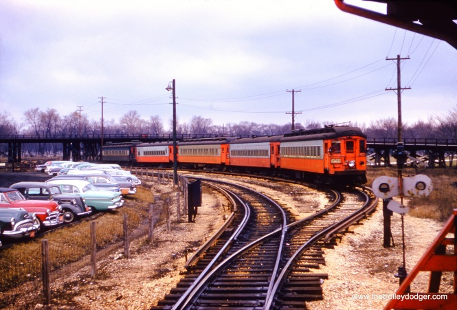 "On March 14, 1957, photographer Monty Powell captured this view of a CA&E train on the midday storage track at the DesPlaines Avenue terminal in Forest Park. Car 421, built in 1927 by the Cincinnati Car Company, is at the head of a five-car train. In the background, you can see the wooden trestle, used by CTA ""L"" trains to turn around. We are looking to the west."