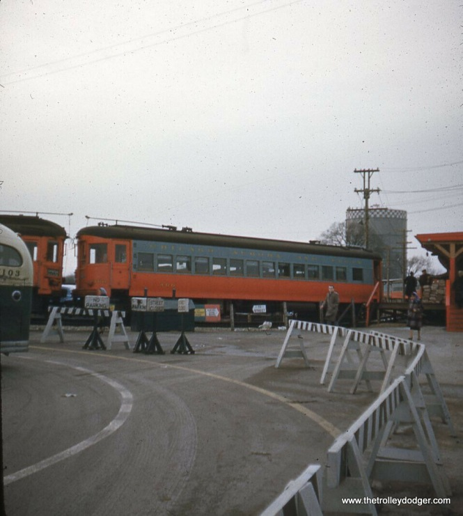 "The CA&E train loops around, in close proximity to a bus, which presumably would either be CTA's Route 17, going to Bellwood and Westchester (it replaced the Westchester branch of the ""L"" in 1951) or one of the various Chicago & West Towns routes."