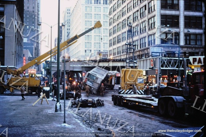 "Accident photos are a sensitive and controversial topic in the railfan field. Some don't think they should be shown at all, while others believe they are an important part of history. This is the aftermath of the 1977 accident where one CTA train ran into another, right at the corner of Wabash and Lake, and pushed some ""L"" cars off the structure. Since that tragedy, where several people lost their lives, additional steel has been added to the structure to prevent a reoccurence. This is a Mark Llanuza photo."