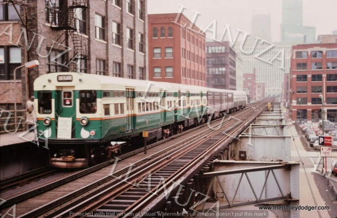 "This Mark Llanuza picture from December 1982 says it is a ""last run."" I can't make out what the sign says, but at the very least, it's a six car CTA ""L"" train, made up of three sets of 6000-series cars, each painted different colors."