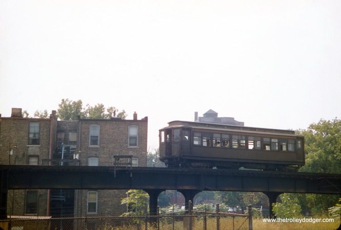 "In August 1957, CTA Met car 2920 approaches the eastern end of the Kennwood ""L"" branch at 42nd Place. This was one of the only locations along the line that used steel structure. The great majority of trackage was on Chicago Junction Railway embankment. There was a yard at this end of the line that had not been used in many years. Service was abandoned on Kenwood soon after this picture was taken. The photographer was standing on the nearby embankment."