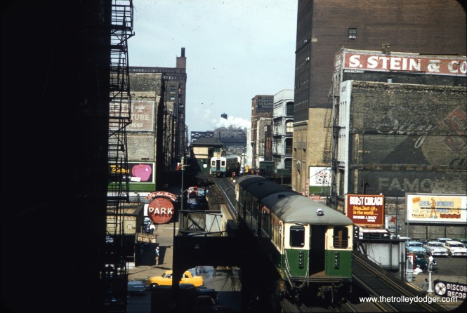 "This is the Chicago Loop ""L"" looking west along Lake Street in August 1957. Trains on the Loop ran in a counterclockwise direction. We see trains of 6000s (rear) and 4000s (near). The 6000s are a westbound Douglas Park train, operating at this time via a portion of Lake-- the same path that Pink Line trains take today. It is taking a jog around the old Tower 18, which was replaced in 1969 in conjunction with the through-routing of the Lake and Dan Ryan lines."