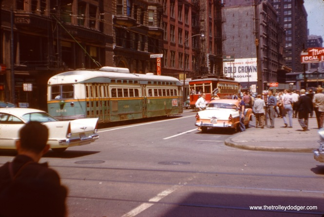A downtown photo stop on the May 25, 1958 streetcar fantrip. These later trips were held on weekends, since in these years, the CTA substituted buses for streetcars on some of the remaining lines. So, the fans could have all the photo stops they wanted. It was also typical to pair one of the older red cars with a PCC. On this trip, the 144 was paired with car 4384. (J. W. Vigrass Photo)
