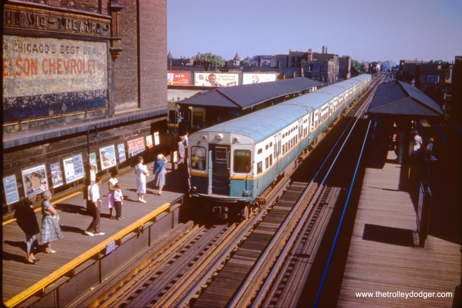 "A southbound Jackson Park ""B"" train approaches the Belmont station on July 3, 1961. At left is the Vic Theater. Notice a Ravenswood train is also entering the station on the outer track."