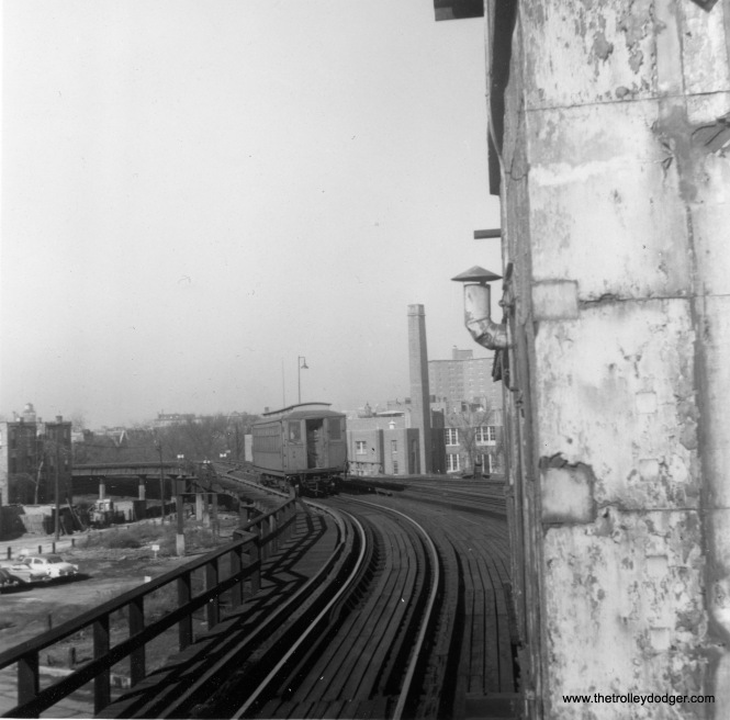 "This is the view looking west from the east terminal of the Kenwood branch at 42nd Place. There was a short stretch of steel structure, before the line ran on an embankment owned by the Chicago Junction Railway. Ross Harano: ""This view is also looking north. The photo was taken from the north end of the platform next to the control tower building. The tall building in the background is one of the first CHA buildings on the lakefront at Lake Park and Oakwood Boulevard. The railroad tracks that ran with the ""L"" tracks went east over the Illinois Central tracks and ran south."""