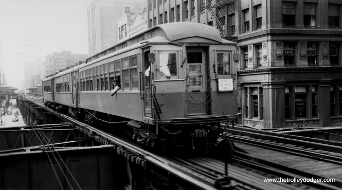 "I find this picture of car 1109 and train interesting for a number of reasons. It took a while to figure out where this is, but I believe it is on the Wabash leg of the Loop ""L"" heading north at Jackson. This area was, for many years, Chicago's ""music row,"" and Kimball Pianos is at right. Since we are south of Adams, the station in the rear is Congress and Wabash, which was closed in 1949 and removed soon after, as Congress was widened for the expressway project. The train is an Evanston Express, going to Wilmette, but also mentions Skokie as a destination. Niles Center changed its name to Skokie in 1941, so this picture dates to the 1940s. Then, as now, it is not advisable to put your head or arms outside the car window."