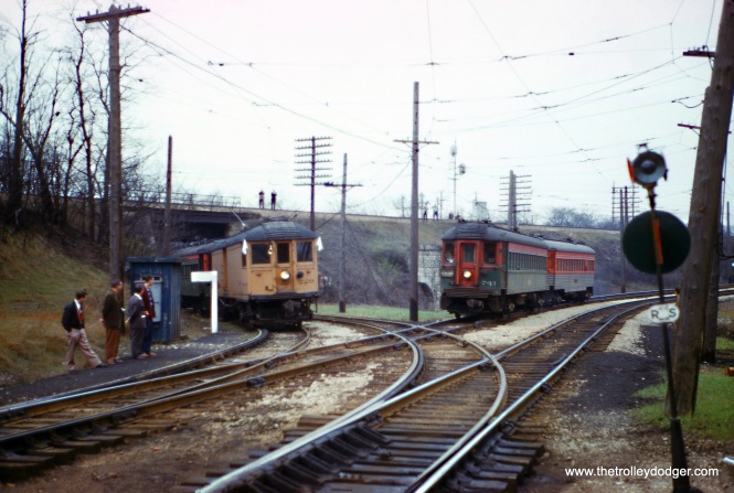 "The late Gordon E. Lloyd took this picture at North Chicago Junction on April 23, 1961. Chuck W. notes, ""The fan trip train on the left, is coming off the Shore Line Route. The train on the right, is the mainline to Chicago, which will split at Upton Junction, with the main line continuing on the Skokie Valley Route and the other branch heading to Libertyville and Mundelein."""