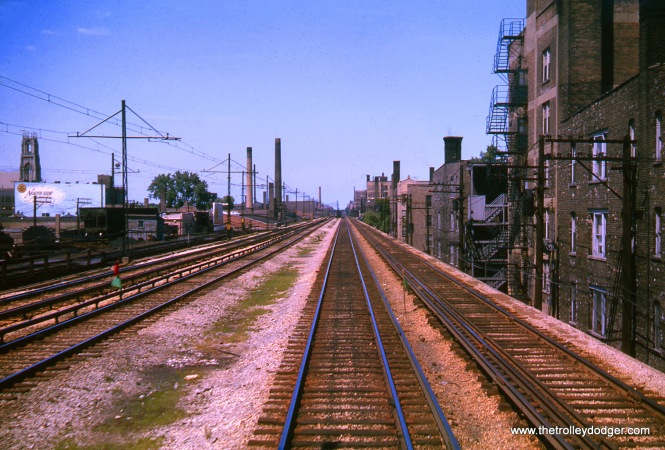 Here, in August 1963, we are just north of the Berwyn station on the North-South main line. Off to the left, there was Lill Coal and Oil, which used freight service on the 'L' until 1973. In this photo, you can see part of their siding heading off from the freight track, which has overhead wire. Lill was the last freight customer the CTA had. Once they stopped using the service, the CTA was able to eliminate freight. This was a carryover from the days when this portion of the route started out as part of the Milwaukee Road. That railroad interchanged with the rapid transit just north of Irving Park Road. Freight cars were hauled by electric locomotives using overhead wire. There was a ramp up to the 'L' structure near Montrose.