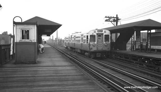 "In this view, taken around July 1, 1957, we see a westbound Garfield Park train at the Kedzie station, which was not in the direct path of the Congress Expressway. The tall smokestack in the distance belonged to the old Garden City Laundry at 3333 W. Harrison. Here, the ""L"" was south of the expressway, and at other points, it was north of the highway. The station off in the distance is St. Louis (3500 W.). Both stations remained open until 1958."