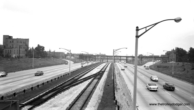 "This picture, and the next one, were taken around July 1, 1957 from the Kedzie Avenue bridge over the then-Congress Expressway, looking east towards Sacramento Boulvard. Tracks are in place for the Congress median line, and in the distance, we can also see where the Garfield Park ""L"" crossed the highway. East of Sacramento, there was a ramp, leading down to Van Buren, where there was a temporary right-of-way at ground level. Tracks were in place for the new line at this time, but as you can see, there was no third rail yet. There is still a crossover at this location. Notice that there were support columns for the ""L"" right in the middle of the highway. It is inconceivable that this would be done today."
