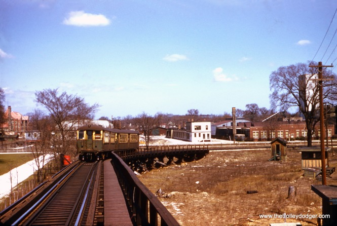 "Now here is a very unusual view, taken on April 14, 1957 from the wooden trestle used by Garfield Park ""L"" trains to loop around at Forest Park circa 1953-59. This arrangement was necessary due to the separation of CTA and CA&E tracks, when the latter cut back service due to the Congress Expressway construction project in the city. Interurban trains turned on a loop between the CTA tracks on the east side of the terminal, while CTA trains went up and over the CA&E on the west end. To get this picture, the photographer either had to be inside a train, or on the walkway. This is only the second such picture I have seen, and the view looks to the north. In the background, you can see the Chicago Great Western freight tracks, abandoned in the early 1970s. The terminal area has been redone twice since then, and the buildings at right in the background are where a parking lot is now. The Altenheim retirement home (at left), built in 1886, is still there today at 7824 W. Madison Street. A two-car train of CTA ""Baldy"" 4000s negotiates the loop."