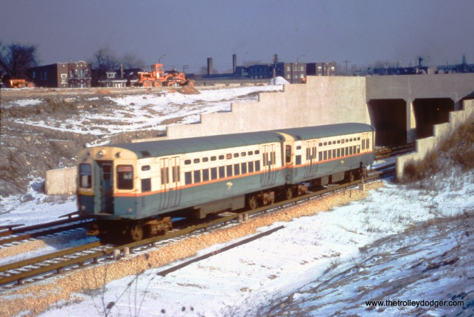 An eastbound two-car train of single car units, including car 8, are about to enter the Lotus Tunnel in March 1960. Construction of the Congress Expressway was well underway just to the north. The new highway opened in this area later that year.