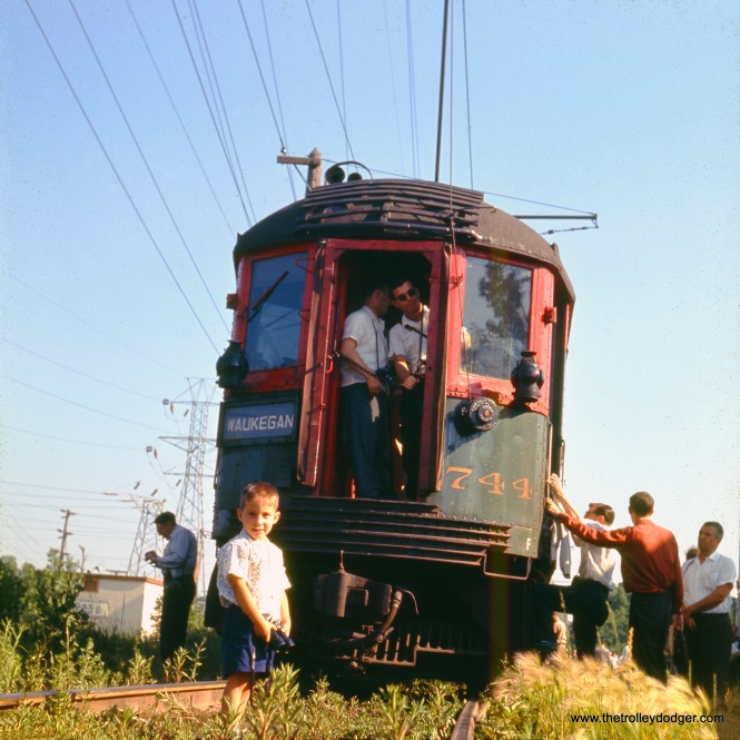 "The date is not known, but this must be a photo stop along the North Shore Line's Skokie Valley Route. We can only imagine how old the young boy at left is today, shown holding a pair of binoculars. This must be a siding of some sort. The original image was shot on size 127 Ektachrome film, a larger format that 35mm, but one that could still be mounted in a 2x2 mount-- what people used to call a ""superslide."" This term is also used to describe slides shot with size 828 film, which was slightly larger than 35mm."