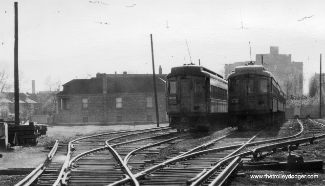 "The CA&E owned everything west of Laramie Avenue, including Lockwood Yard, shown here circa 1930 or so (by the looks of the auto at left). We are looking west and that's Loretto Hospital in the distance, opened in 1923. Cars 418 and 431 are visible. Interestingly, the yard used overhead wire instead of third rail at this time. You can see a fence at the west end of the yard, and what appear to be a couple small bumper posts at track's end. After the Garfield Park ""L"" was replaced by the CTA Congress median line, an alleyway was put in here, approximately where the two trains are. The house is still there, as you will see in the pictures that follow, and, it seems, one of the posts that supported trolley wire. However, the homes at left, on Flournoy Street (700 S.) are gone, replaced by expressway. This portion of yard and right-of-way is now occupied by light industry."