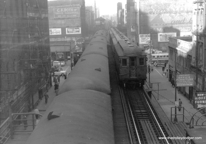 On February 19, 1957, we are looking west from the transfer bridge at Clark and Lake. A five-car Evanston Express train is at right, made up of wood cars in their final year of service.