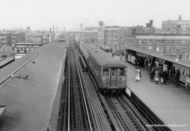 "The view looking west at 40th and Indiana Avenue on the South Side ""L"". An 8-car Jackson Park train of 4000s is going to head north to Howard, and a train of southbound 6000s is off in the distance. The extra wide platform at right was extended in 1949, when the CTA turned the Kenwood branch into a shuttle operation. Riders could change here for that line and the Stock Yards branch. The date is April 13, 1954."
