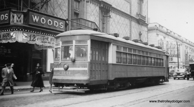 CTA 3131, a one-man car operating on Route 16 - Lake Street, stops in front of the Woods Theater, located at 54 W. Randolph Street. The film 12 O'Clock High dates the picture to 1949. The Woods closed in 1989.