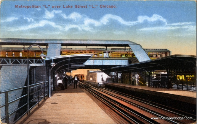 "Postcards like this were based on black-and-white photos, although the finished product, since it is traced, ends up looking more like a drawing. Once the four ""L"" lines were put under consolidated management in 1913, free transfers between lines were permitted. Here, the Met ""L"" along Paulina crossed the Lake Street ""L"", the only place on the entire system where two competing lines crossed, so Lake Street Transfer station was built. Met trains went downtown anyway, but it's possible some riders might have been able to save a few minutes by switching to a Lake Street train. The view looks east."